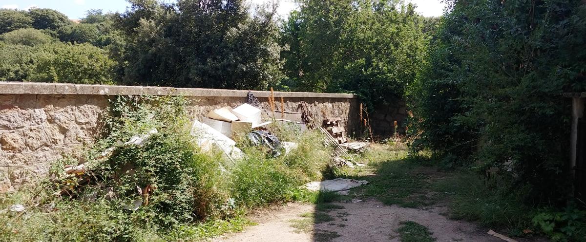 Tifiuti, erbacce, cumuli di materiali da discarica abbandonati.